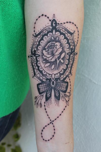 Tatuaggio Braccio Medaglione di Full Circle Tattoos